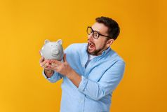 Concept of Finance and business.  man with  piggy Bank on  yellow background color stock images