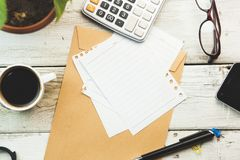 Concept for Financial accounting. Calculator and paper, cup of coffee, pencils and eraser on white wooden table stock photography