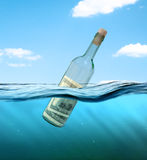 Concept. Financial assistance. Bottle of money floating in the water. bundle of dollars floating in the bottle Stock Photography
