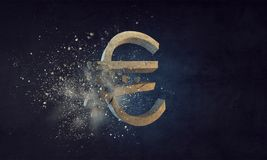 Concept of financial crisis. Mixed media. Cracked stone euro sign on dark background. Mixed media Stock Photo