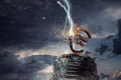 Concept of financial crisis. Mixed media. Lightning striking stone euro sign. Mixed media Stock Photo