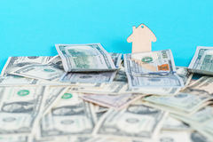 The concept of financial savings to buy a house. Mini model house behind moneys background. Stock Photography