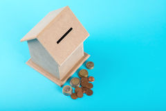 The concept of financial savings to buy a house. Money box and coins isolated on blue background. Stock Photos