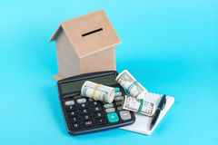 The concept of financial savings to buy a house. Money box, dollars and calculator  on blue background. Royalty Free Stock Photography