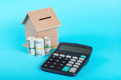 The concept of financial savings to buy a house. Money box, dollars and calculator  on blue background. Royalty Free Stock Images