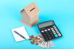 The concept of financial savings to buy a house. Money box, dollars, coins and calculator isolated on blue background. The concept of financial savings to buy a Stock Images