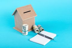 The concept of financial savings to buy a house. Money box, dollars, notebook with pen isolated on blue background. Royalty Free Stock Images