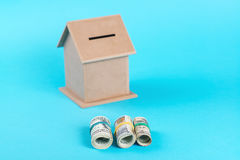 The concept of financial savings to buy a house. Money box, dollars in rolls, isolated on blue background. Stock Photography