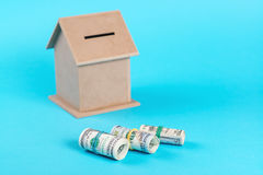 The concept of financial savings to buy a house. Money box, dollars in rolls, isolated on blue background. Royalty Free Stock Image