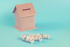 The concept of financial savings to buy a house. Money box, dollars in rolls, isolated on blue background. Toned. Stock Photography