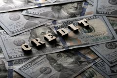 The word CREDIT is lined with wooden letters on the background of hundred-dollar bills. The concept of financial transactions and royalty free stock images