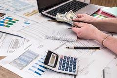 Concept financier avec l'ordinateur portable, le dollar et le rapport de gestion, le stylo-plume et la calculatrice Photographie stock