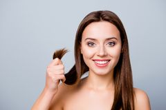 Concept of finding a good solution in treating damaged hair ends. Pretty cute smiling woman is showing her healthy hair, isolated on grey background Royalty Free Stock Image