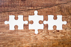 The concept of finding the right solutions in teamwork. Tree connected jigsaw puzzle pieces on wooden background. The concept of finding the right solutions in Stock Images