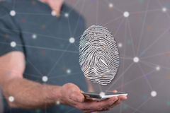 Concept of fingerprint security system. Fingerprint security system concept above a smartphone held by a man in background Royalty Free Stock Photography