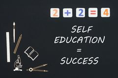 School supplies placed on black background with text self education success. Concept first class school, text self education success with wooden miniatures Royalty Free Stock Photos