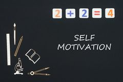 School supplies placed on black background with text self motivation. Concept first class school, text self motivation with wooden miniatures school supplies and Stock Images