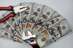 Concept of fixing currency of money and tools. Wrench, Pliers, screwdriver and dollars on a gray background stock image
