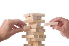 Concept fonctionnant d'équipe : deux mains des hommes plaçant les blocs en bois dans une tour faite avec les blocs en bois avec image stock