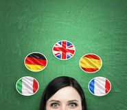A concept of foreign language studying process. A foreseen of the brunette girl surrounded by icons of european flags. Green chalkboard background stock images