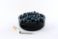 Concept: forget the cigarettes and eat fruits. Ash bowl full of fruits with a broken cigarette near Stock Photos