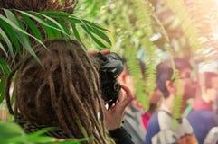 Concept - fotografie op een excursie Fotograaf die met dreadlocks op zijn hoofd in serre botanische tuin schieten royalty-vrije stock foto