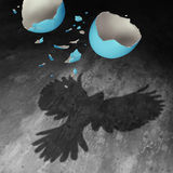 Concept Of Freedom. As a falling broken egg shell in the air creating a cast shadow of a bird with open wings as a positive motivation metaphor for stock illustration