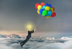 Concept of freedom. A businessman being lifted by balloons with glowing light bulb a head. Concept of idea Royalty Free Stock Photos