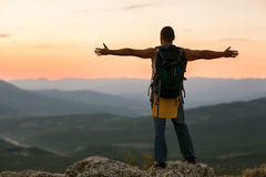 Concept of freedom. Guy in the mountains at sunset. the concept of freedom Royalty Free Stock Photo