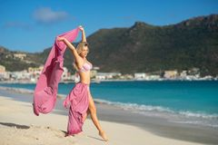 Concept of freedom and happiness. Happy woman on the beach in summer with flying pink silk.  royalty free stock image