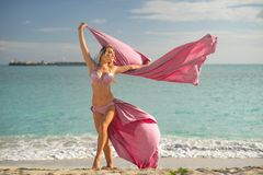 Concept of freedom and happiness. Happy woman on the beach in summer with flying pink silk.  royalty free stock photo