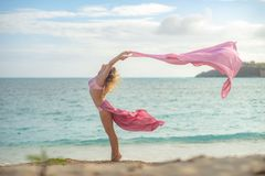 Concept of freedom and happiness. Happy woman on the beach in summer with flying pink silk.  royalty free stock photography
