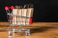 Concept of friday sale with shopping trolley, paper bags on wood. En background over black, close up Royalty Free Stock Photo