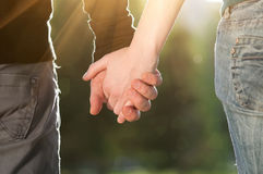 Concept of friendship and love of man and woman. Concept shoot of friendship and love of man and woman: two hands over sun ray and nature stock image