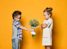 Concept of friendship, quarrel, date. Little boy gives a bouquet of daisies to his girlfriend a girl. The girl angrily folded her arms in front of her and did royalty free stock photo