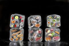 Concept of frozen products: fruits, vegetables, fishs, meat, spices herbs, pastry, were frozen inside ice cubes on black. Concept of frozen products: fruits stock photos