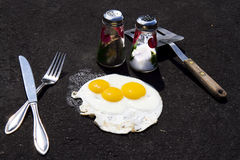 Concept - Frying Eggs Hot Asphalt Driveway Royalty Free Stock Images