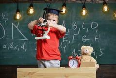 Concept futé d'enfant Premier ancien intéressé à étudier, apprenant, éducation Enfant sur le visage occupé près du microscope Gar photographie stock