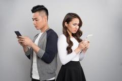 Concept futé de dépendance de téléphone Jeunes couples asiatiques utilisant l'Internet Image libre de droits