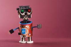 Concept futuriste de robot Mécanisme drôle de jouet, tête en plastique noire, yeux rouges verts colorés, mains bleues de fil Copi Photographie stock libre de droits