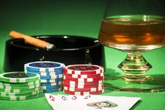 The concept of gambling, cards and chips with a glass of cognac and a cigar. The concept of gambling, playing cards and chips with a glass of cognac and a cigar royalty free stock photography