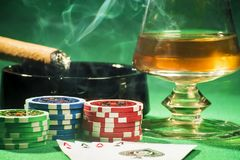 The concept of gambling, cards and chips with a glass of cognac and a cigar. The concept of gambling, playing cards and chips with a glass of cognac and a cigar stock photo