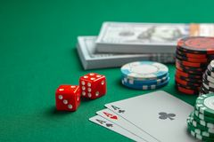 Concept of gambling in casino, sports poker. Playing cards with dice and colored chips with cash money dollars on green table. Concept of gambling in casino stock photography