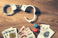Concept of gambling illegally, showing handcuff, play cards, dic Stock Image