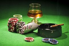 The concept of gambling, cards and chips with a glass of cognac and a cigar. The concept of gambling, playing cards and chips with a glass of cognac and a cigar royalty free stock images