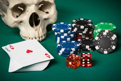 Concept of gambling. Skull, deck of cards with an ace and a joker on top, chips and dice on a green table Stock Images