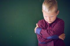 Concept geïntimideerde schooljongen Droevig en boos koestert weinig Kaukasische jongen zich met zijn handen die zich op bevinden stock fotografie