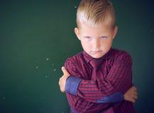 Concept geïntimideerde schooljongen Droevig en boos koestert weinig Kaukasische jongen zich met zijn handen die zich op bevinden royalty-vrije stock afbeeldingen