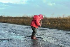 Concept - gelukkige kinderjaren Meisjespelen in vulklei, kinderen` s pret, onvergetelijke ogenblikken, vuile en natte schoenen, p royalty-vrije stock foto's