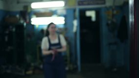 The concept of gender equality. A pretty young woman in a work uniform, working at the machine, the frame in a blur, and then come